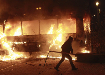 A pro-European integration protester walks past a burning police van during a rally near government administration buildings in Kiev
