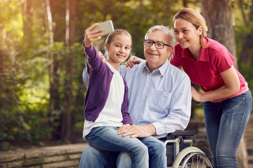 daughter with her disabled father in wheelchair and granddaughter using phone for selfie.