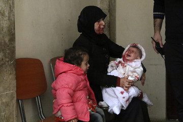 A survivor of a barrel bomb holds her crying baby in a hospital in Aleppo's al-Sakhour district