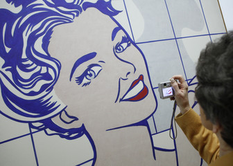 A woman takes a picture of one of Roy Lichtenstein's paintings at the opening of an art exhibition in Vienna