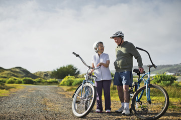 Happy elderly couple chat together as they take a break from biking along a country road.