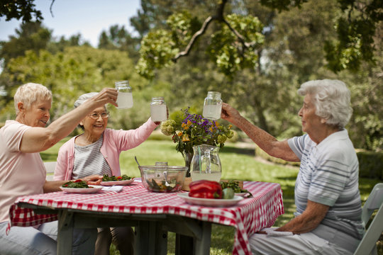 Senior friends make a toast before a healthy lunch outside.