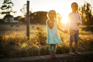 Two young blond sisters hold hands at the side of a country road at sunset.