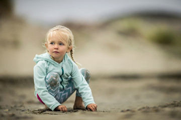 Portrait of a young blond girl playing in the sand at the beach.
