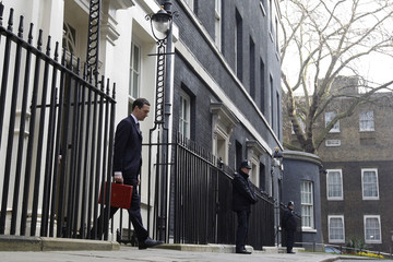 Britain's Chancellor of the Exchequer, Osborne, holds up his budget case for the cameras as he stands outside number 11 Downing Street in central London