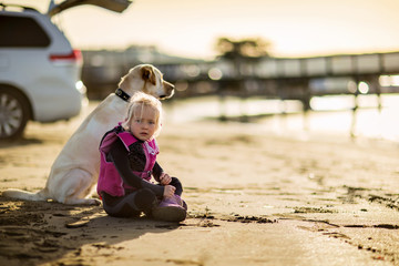 Young girl sitting on the beach with her dog.
