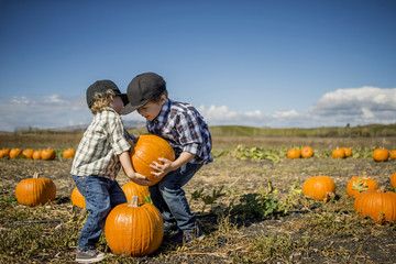 Two young boys trying to lift pumpkin.
