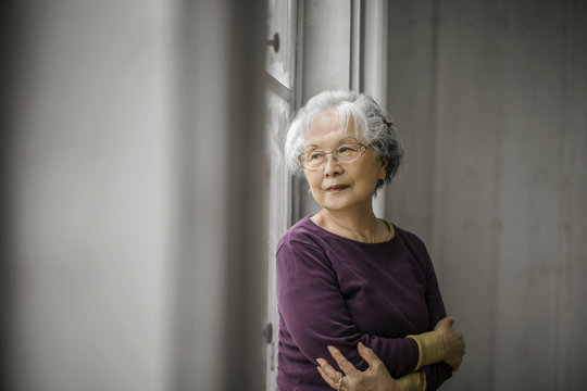 Portrait of a pensive senior woman looking out a window.