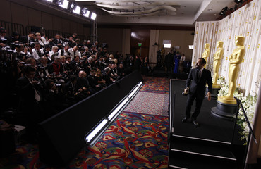 "Farhadi, director of Iranian film ""A Separation"", walks offstage with his Foreign Language Film award, in Hollywood"