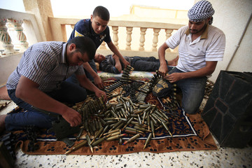 Rebel fighters prepare ammunitions at their position in the outskirts of Zlitan near Misrata's western front line
