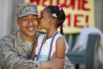 Young girl giving her father a kiss on the cheek.