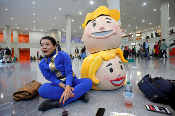 Vanessa Pham sits with the heads of Vault Boy and Vault Girl at New York Comic Con in Manhattan