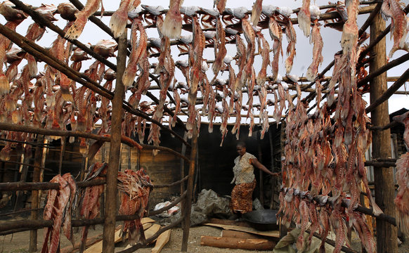 """A fish trader is seen past fish skeletons set out to dry on wooden poles at her stall at the Obunga """"mgongo-wazi"""" fish frying market in Kisumu"""