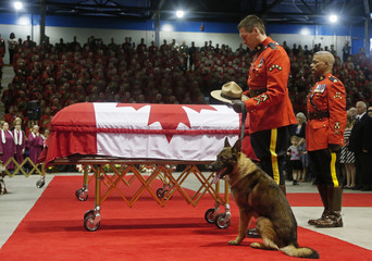 A Royal Canadian Mounted Police officer with the hat and dog of K-9 officer David Ross, who was killed last week along with two other RCMP officers, pauses in front of his casket during a regimental funeral in Moncton