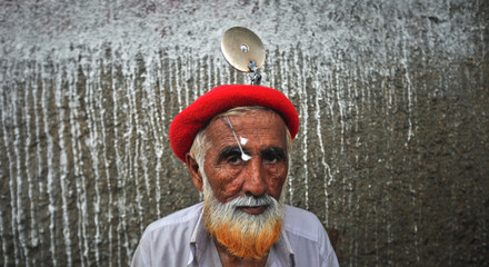 Ghayyaz-Uddin, 52-year-old ear cleaner, wears his tools as he waits for customers along a sidewalk in Karachi