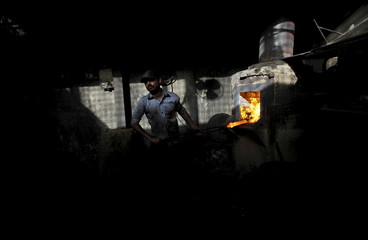 A laborer pulls a heated iron rod with a pair of foundry tongs to make tools at a workshop in Karachi