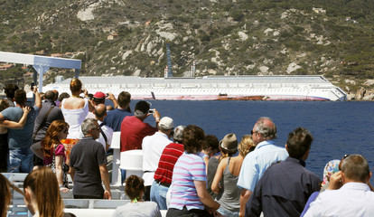 People take pictures from a ferry of capsized cruise liner Costa Concordia near the harbour of Giglio Porto