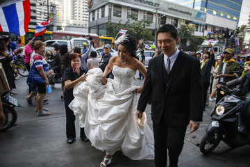 A bride and a groom arrive to take pictures ahead of their wedding as anti-government protesters march during a rally at a major business district in Bangkok