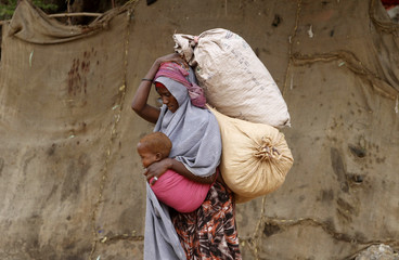 A displaced Somali woman carries a child and her belongings as she arrives at a temporary dwelling after fleeing famine in the Marka Lower Shebbele regions to the capital Mogadishu