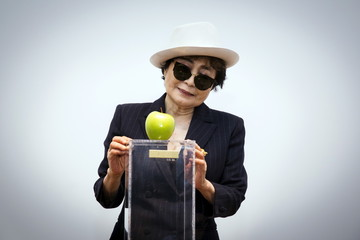 "Artist Yoko Ono interacts with the exhibit ""Apple"" at the Museum of Modern Art exhibition dedicated exclusively to her work in New York"