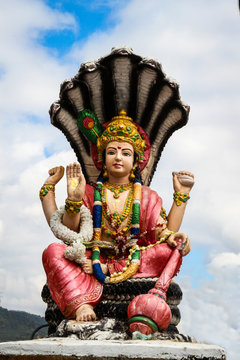 Lord Vishnu statue in a sitting position against blue sky.