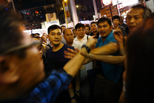 A man points at people who started small scuffle with pro-democracy protesters at barricades at Mongkok shopping district in Hong Kong