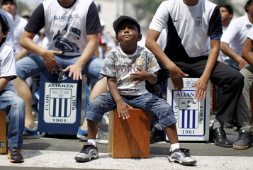 A boy plays his cajon, a popular Peruvian instrument, during the 8th International Festival of the Peruvian Cajon in Lima's Plaza Mayor