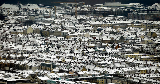 The snow covered roofs of residential buildings are pictured in Munich