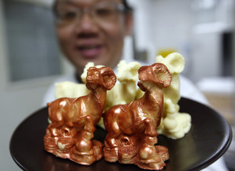 A chef shows goat-shaped chocolates, two of them painted with edible gold powder, as he prepares to make a cake celebrating the upcoming Chinese Lunar New Year, during a photo opportunity at a kitchen of Kerry Hotel in Beijing