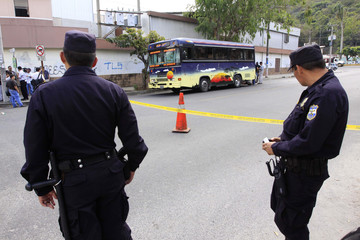 Police officers stand guard near crime scene where woman named Orellana was killed inside public bus by suspected gang members in Santa Tecla, on the outskirts of San Salvador