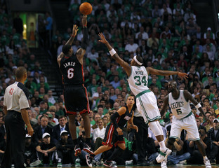 Miami Heat's James shoots over Boston Celtics defenders Pierce and Garnett during the first quarter of their NBA basketball game in Boston