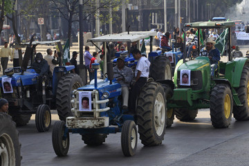 Farmers drive tractors with pictures of missing trainee teachers during a protest in Mexico City
