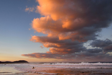 A surfer holding her board wades through the surf as clouds above are lit by the setting sun at Mollymook Beach on the south coast of New South Wales
