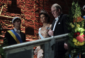 Sweden's Queen Silvia is escorted by Storch, Chairman of the Board of the Nobel Foundation as they arrive at the Nobel banquet at Stockholm's City Hall December