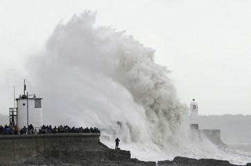 Crowds gather to watch as waves crash against the harbour wall at Porthcawl in south Wales