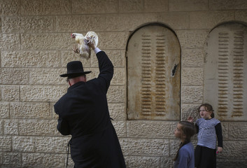 An ultra-Orthodox Jewish man holds a chicken as he performs the Kaparot ritual in Jerusalem ahead of Yom Kippur