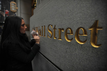 A woman writes on a paper on a wall next to the New York Stock Exchange in New York
