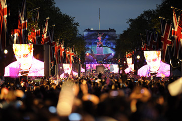 Spectators watch Elton John on giant screens during the Diamond Jubilee concert in front of Buckingham Palace in London