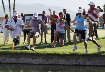 Lewis of the U.S. celebrates winning the LPGA Kraft Nabisco Championship golf tournament by jumping into Poppie's Pond with her caddie and family in Racho Mirage
