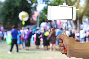 Smart phone on a selfie stick with hand at a graduation. Blank screen with copy space