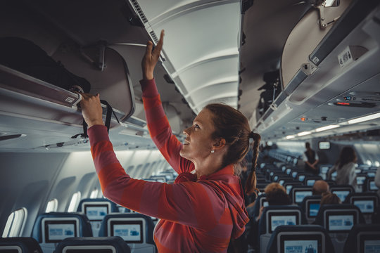 The young girl placed her hand luggage into the compartment on the plane