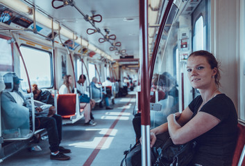 Woman travels overground metro in the afternoon in Canada