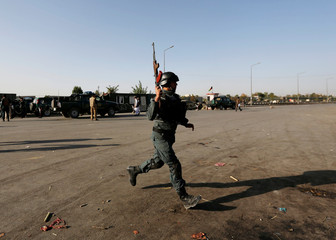 An Afghan policeman arrives at the site of a suicide attack in Kabul