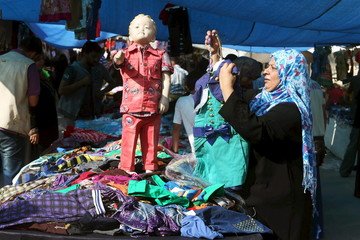 Palestinian woman shops in a market ahead of the Eid al-Fitr holiday marking the end of Ramadan, in the central Gaza Strip