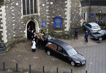 Family members follow behind as pall bearers carry the coffin of former Watford and England soccer manager Graham Taylor away from his funeral in Watford