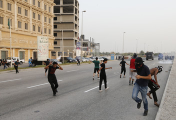 Anti-government protesters run for cover as riot-police disperse them with sound grenades in the village of Selah