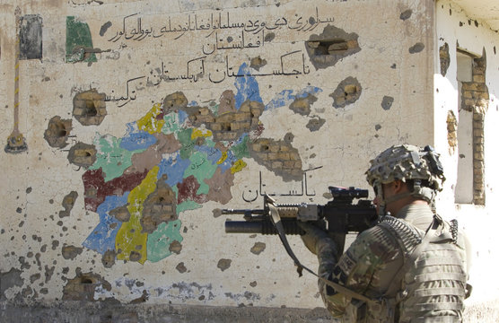 A U.S. Army soldier of 5-20 Infantry Regiment attached to 82nd Airborne Division, aims his rifle in front of a bullet riddled map of Afghanistan in Kandahar province