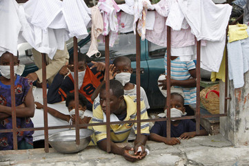 Earthquake survivors wearing masks are seen in a street of Port-au-Prince