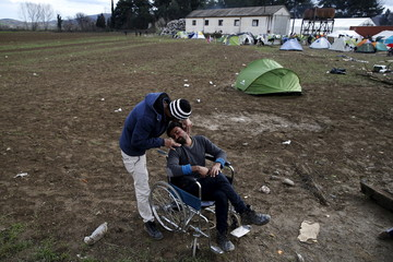 Migrants who are waiting to cross the Greek-Macedonian shave each other at a makeshift camp near the village of Idomeni