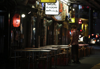 A member of staff stands near empty tables outside a bar in Tokyo
